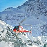 Elicottero rosso alle alpi svizzere vicino alla montagna di Jungfrau Fotografia Stock Libera da Diritti