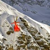 Elicottero rosso in volo nelle alpi di inverno Immagini Stock Libere da Diritti