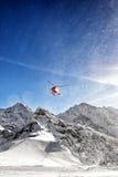 Elicottero rosso in volo nelle alpi di inverno con la polvere della neve Fotografia Stock