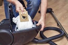 Eliminación de la bolsa anti polvo llena de un aspirador Foto de archivo libre de regalías