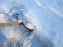 Eliminación de nieve con una pala después de nevadas imagenes de archivo