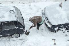 Eliminación de nieve de los coches fotografía de archivo libre de regalías