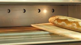 Eliminando con il pane al forno caldo della pala dal forno video d archivio