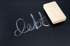 Eliminating Debt. The word DEBT written in chalk on a chalkboard being rubbed out by an eraser Royalty Free Stock Photos