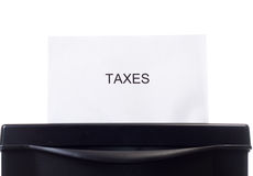 Eliminating Taxes. Closeup view of a single paper with the word taxes on it, going through the shredder Stock Photography