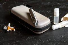 Elimination of tobacco smoking electronic cigarette on dark background Royalty Free Stock Images