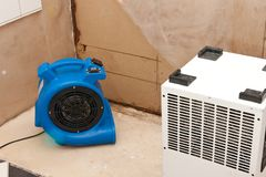 Water damage restoration. Elimination of water damage with fan and dryer stock photos