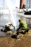 Elimination of water leaks. Two working spend the leak of water Royalty Free Stock Images