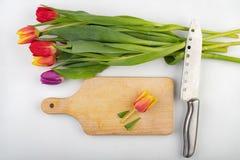 Elimine a cabe?a de uma tulipa em uma placa de corte da cozinha Flor de corte na cozinha fotografia de stock