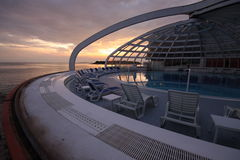Eliptic pool with opened roof. Part of circle swimming pool with opening glass roof by the sea in the evening stock photos