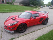 Elise rojo de Lotus parqueado en vecindad suburbana Imagenes de archivo