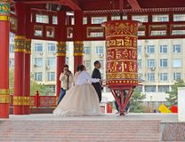 ELISTA, RUSSIA. The groom and the bride spin a prayer wheel with a mantra of Ohms of Manya Padme Hum. Pagoda of Seven Days. ELISTA, RUSSIA - APRIL 21, 2017: The royalty free stock photo