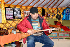ELISTA, RUSSIA. The Kalmyk man plays on a dombra in the tilt cart Stock Images