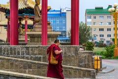 ELISTA, RUSSIA - MAY 6, 2018: Buddhist monk walks near temple in Elista. ELISTA, RUSSIA - MAY 6, 2018: Unidentified Buddhist monk walks near temple in Elista. It Stock Image