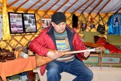 ELISTA RYSSLAND Den Kalmyk mannen spelar på en dombra i lutandevagnen Arkivbilder