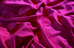 Elite bedclothes. Red wrinkled fabric texture background Royalty Free Stock Photos
