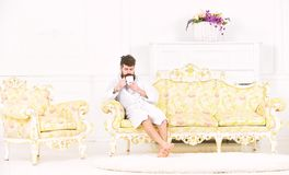 Elite leisure concept. Man with beard and mustache enjoys morning while sitting on luxury sofa. Man on sleepy face in. Bathrobe, drinks coffee, in luxury hotel royalty free stock images