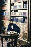 Elite lifestyle concept. Aristocrat on smiling face holds book. Man in classic suit sits in vintage interior, library, book shelves on background. Oldfashioned stock photography