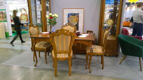 Elite modern furniture made of natural wood at exhibition. Premium table and chairs. Brown сomfortable armchair. Design and decor
