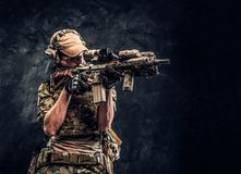 The elite unit, special forces soldier in camouflage uniform holding an assault rifle with a laser sight and aims at the. Target. Studio photo against a dark stock photo