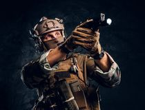 Elite unit, special forces soldier in camouflage uniform holding a gun with a flashlight and laims at the target. Studio photo against a dark textured wall royalty free stock photo