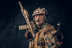 Elite unit, special forces soldier in camouflage uniform posing with assault rifle. Studio photo against a dark textured wall royalty free stock photo