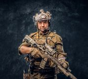 Elite unit, special forces soldier in camouflage uniform posing with assault rifle. Studio photo against a dark textured wall stock images