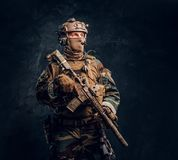 Elite unit, special forces soldier in camouflage uniform posing with assault rifle. Studio photo against a dark textured wall stock image