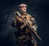 Elite unit, special forces soldier in camouflage uniform posing with assault rifle. Studio photo against a dark textured wall royalty free stock photography