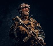 Elite unit, special forces soldier in camouflage uniform posing with assault rifle. Private security service contractor in camouflage uniform posing with stock photo