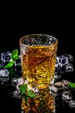 Elitedrank voor mannelijke ontspanning glasse van whisky en ijs en verse munt op zwarte achtergrond, exemplaarruimte stock afbeeldingen