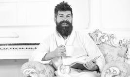 Elitfritidbegrepp Man sömnigt i badrocken, drinkkaffe, läser boken i lyxigt hotell i morgonen, vit bakgrund royaltyfri fotografi