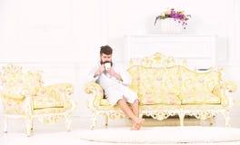 Elitfritidbegrepp Mannen med skägget och mustaschen tycker om morgon, medan sitta på den lyxiga soffan Man på sömnig framsida in royaltyfria bilder