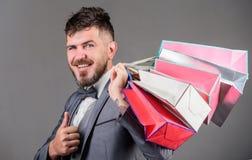 Elity butik Mężczyzny brodaty elegancki biznesmen niesie torby na zakupy na popielatym tle Robi robić zakupy radosnego enjoy obraz stock