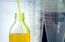 Elixir. Yellow liquid filling a bottle stock photos
