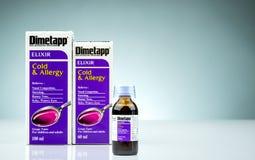 Elixir de Dimetapp en la botella ambarina con la taza de medición y empaquetado aislada en fondo de la pendiente Descongestionant imágenes de archivo libres de regalías