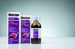 Elixir de Dimetapp na garrafa ambarina com copo de medição e empacotamento isolada no fundo do inclinação Descongestionante nasal imagens de stock