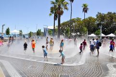 Elizabeth Quay: In The Mist. PERTH,WA,AUSTRALIA-FEBRUARY 13,2016: Waterpark with mist spraying in the Elizabeth Quay development with families playing and Stock Photos