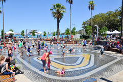 Elizabeth Quay Waterpark. PERTH,WA,AUSTRALIA-FEBRUARY 13,2016: Waterpark in the Elizabeth Quay development with families playing and tropical trees in Perth Royalty Free Stock Photos