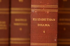 Elizabethan Drama. Closeup, selective focus image of an old worn book spine. Background of additional out of focus books Stock Photos