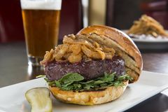 Elk Burger and Beer. Delicious Elk Burger and Beer served on a white plate with a pickle royalty free stock images