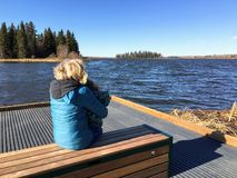 A woman and her granddaughter enjoying the views of the beautiful Astotin lake in Elk Island. Elk Island National Park, Alberta, Canada - October 20th, 2018: A stock photo