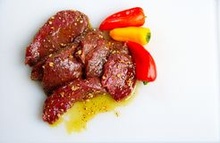 Elk steaks with peppers. Elk back strap steaks that are marinading in olive oil, spices and garlic along with some peppers. These venison steaks are raw stock photography