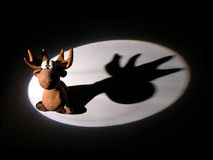 Elk toy in light spot. Elk toy with shadow in light spot royalty free stock images