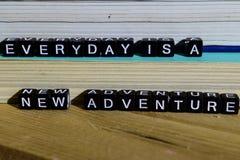 Elke dag is een nieuw avontuur op houten blokken Motivatie en inspiratieconcept royalty-vrije stock afbeelding