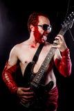 Elkraft gitarrist med svart för elektrisk gitarr, bärande framsidapai royaltyfri bild