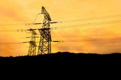 Elkraften driver pylonen på solnedgången arkivbilder