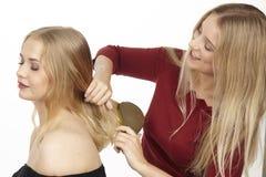 Ella cepilla a su novia el pelo foto de archivo
