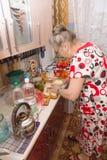 Ella cocina la cena Imagenes de archivo
