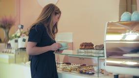 Ella comprador elige delicioso Muchacha atractiva joven, compras de la mujer en la cafetería o pasteles, tortas, torta, macarrone almacen de metraje de vídeo